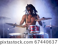 african man sit beating on drums in smoky space 67440637