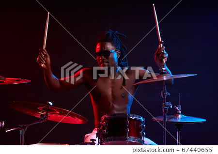 active african man playing on drums set in neon lights 67440655
