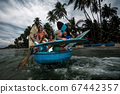 Vietnamese wooden boat with a group of surfers 67442357