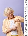 Smiling elderly woman saving euro coin into piggybank and smiling at camera 67442736
