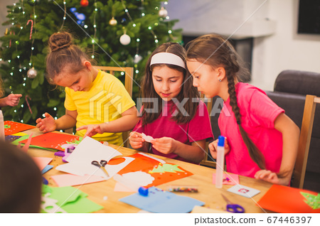 Cooperation and support between kids at Christmas workshop 67446397
