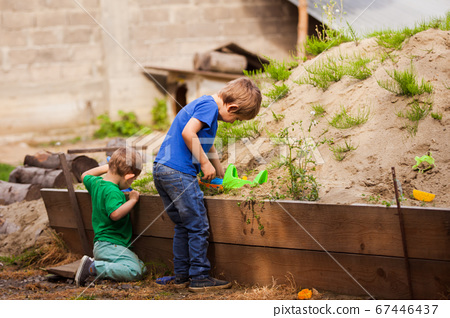 Two little brothers play together in the sandbox 67446437