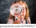 Little girl child looking through a magnifying glass against blackboard. Instagram filter. Back to school. Funny kid face. Big eye 67446627