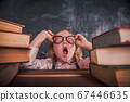 Back to school. Kid in glasses sitting on table with stack of books. Pupil is yawning. Child bored while doing homework 67446635