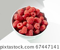 Fresh raspberries in ceramic bowl on white table. Close up photo with sunlight. 67447141