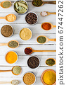 Collection of spicy condiments in spoons and bowls 67447262
