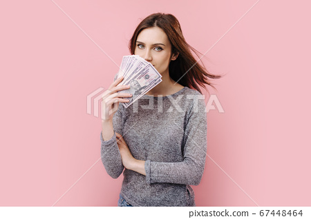 Beautiful girl standing over pink background with money cash 67448464