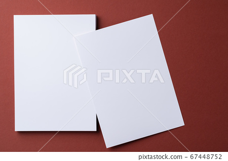 Blank white business cards on burgundy paper background 67448752