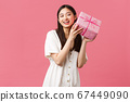 Celebration, party holidays and fun concept. Curious cute excited woman in white dress celebrating birthday, wonder whats inside b-day gift, shaking box and smiling happy, pink background 67449090