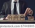 Realtor building houses of wooden blocks 67449905