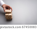 Businessman hand making a stack of wooden pegs 67450083