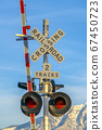 Railroad crossing sign with barrier and red lights 67450723