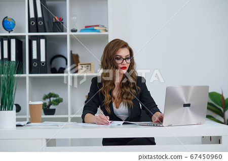 Beautiful business woman in office wearing stylish clothes, makes some notes on paper while sitting at modern cozy office. 67450960