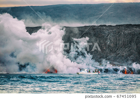 Hawaii volcano eruption boat tour. Tourists on ocean cruise travel activity watching the lava reaching the water with toxic fumes. Dangerous excursion on Big Island 67451095
