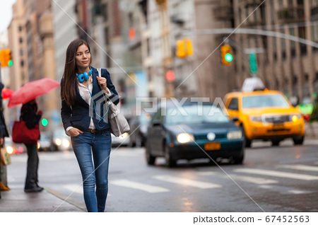 Young Asian professional woman walking home commuting from work in New York city street. Urban people lifestyle commuter in NYC traffic rain day. Chinese girl with purse and headphones for commute 67452563