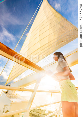 Luxury travel elegant woman on cruise ship yacht on jet set vacation sailing around the world. High end tourism sail boat in sunset 67453748