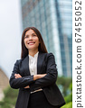 Asian businesswoman confident in Hong Kong. Businesswoman standing outdoor with city urban background in suit cross-armed. Young multiracial Chinese Asian / Caucasian professional in Hong Kong 67455052