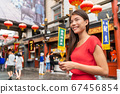 China food market tourist woman walking using phone on Beijing hutong street travel vacation adventure. City lifestyle young Asian girl. Asia summer travel destination. Girl traveling Asia chinatown 67456854