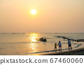 View from the beach with a yellow glowing sun setting in the horizon with an Asian family playing in the water. 67460060