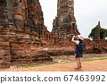Asian girl tourist taking photo of ancient of pagoda temple thai architecture at Wat Chaiwatthanaram is a Buddhist temple in the city of Ayutthaya Historical Park,Thailand,summer vacation,travel conce 67463992