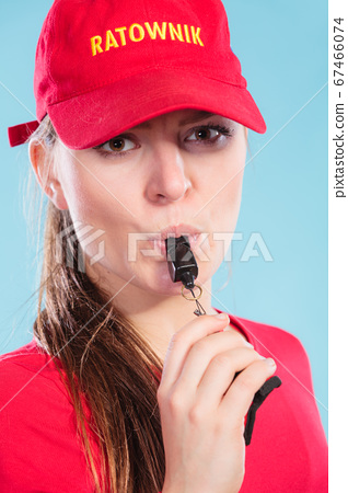 Lifeguard woman in cap on duty blowing whistle. 67466074