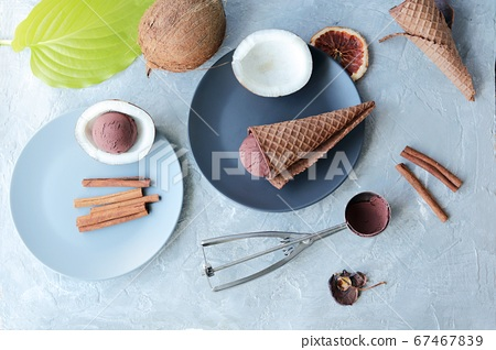 Homemade ice cream in waffle cones, coconuts on the kitchen table, preparing a healthy dessert 67467839