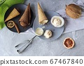 Homemade ice cream in waffle cones, coconuts on the kitchen table, preparing a healthy dessert 67467840