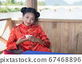 Asian woman drinking from a cup 67468896