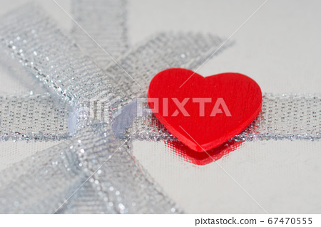 red heart on silver ribbon with bow 67470555