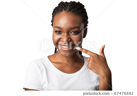 Girl Pointing Finger At Teeth With Braces Posing In Studio 67470892