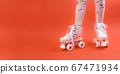 Roller skates on the legs of a urenburg. Retro rollers on a bright background. The concept of 67471934