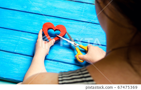 girl cuts the heart with scissors, the concept of breaking relations, quarrels and divorce. Betrayal of the othere. blue background 67475369