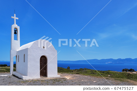 White Greek Orthodox chapel or church on hilltop of seashore against clear blue sky on sunny day.  67475527