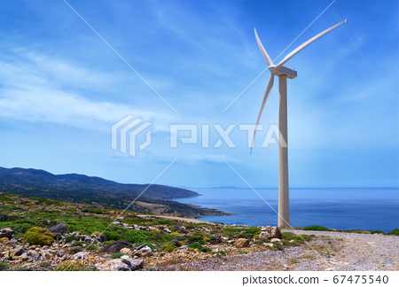 Single windmill turbine on hilltop of seashore in colorful landscape against dynamic blue sky with clouds and winding road. 67475540