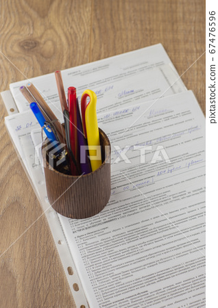 workplace of the businessman: some forms of contracts, filled and empty, and stationery in the pencil case, the space on top 67476596