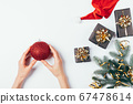 Woman's hands holding red ball Christmas toy 67478614