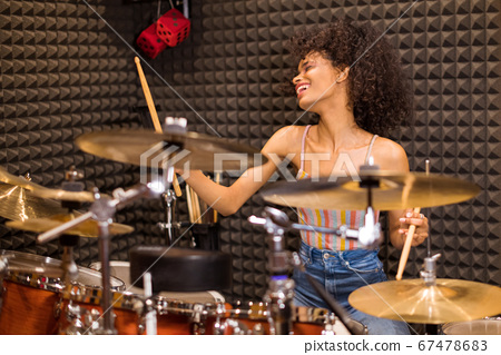 Young black female drummer in a recording studio 67478683