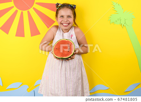 Little girl on a bright background with Italian flag holding a ripe red watermelon in her hands 67481805