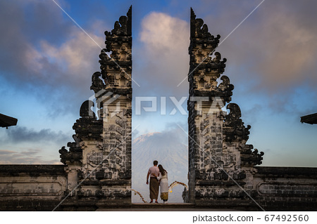 Happy young couple staying in temple gates of 67492560