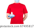 Man in red t-shirt, medical mask and gloves holding wet wipes or tissue isolated 67495817