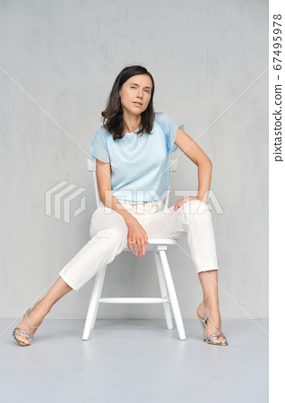 Beautiful lady in blue satin blouse, white jeans and silver stilettos sitts on white chair in studio 67495978