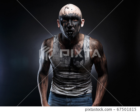 Photo of dirty mad man with black muck in the mouth 67501815