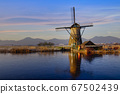 Reflection on a frozen canal of a Dutch windmill 67502439