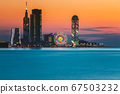 Batumi, Adjara, Georgia. Skyline Of Resort Town At Sunset Sunrise. Bright Orange Evening Sky. View From Sea To Illuminated Cityscape With Modern Urban Architecture, Skyscrapers And Tower. Golden Hour 67503232