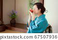 A woman in a kimono drinking alcohol with a cup 67507936