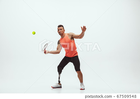 Athlete with disabilities or amputee isolated on white studio background. Professional male tennis player with leg prosthesis training and practicing in studio. 67509548