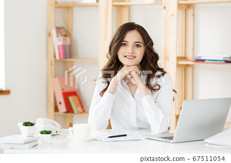 Young attractive woman at a modern office desk, working with laptop and thinking about something. 67511054
