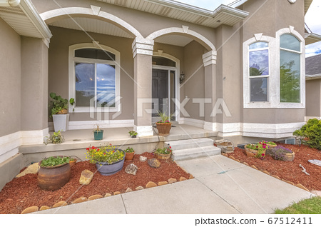 Landscape yard of a home with front porch 67512411