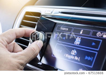 Driver turning volume button of car radio 67513608