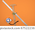Construction measuring tool on orange background. 67522236